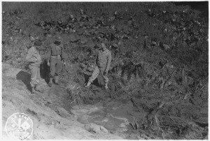 American service men inspect a shell crater after the Japanese attack on Fort Stevens.